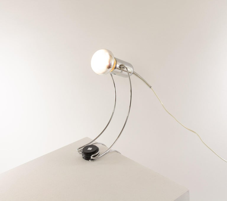 Adjustable chrome table lamp designed by Francesco Fois and manufactured by Reggiani during the 1960s.  The lamp, with its elegant round shapes, can be clamped with its lower part for example to a tabletop. The chrome spot light can be directed in