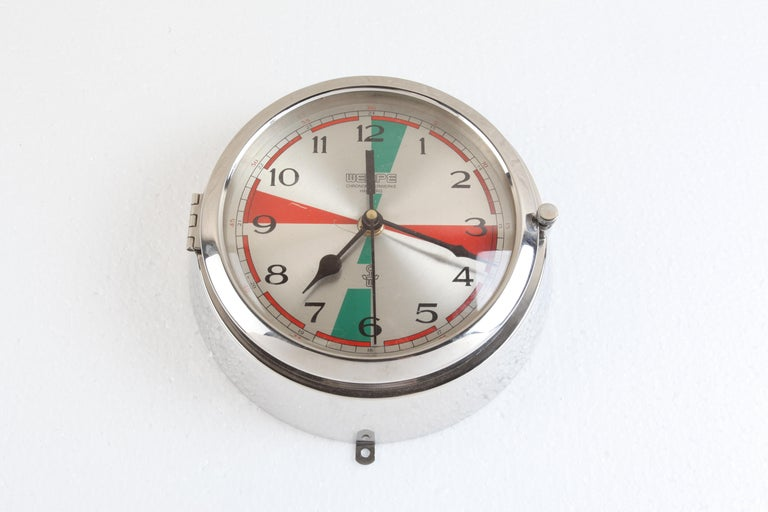 A ship's chrome analog clock used in the radio room, hence the colorful face. The minutes in these zones were meant for silence in the radio room in order to listen for SOS alerts a post Titanic requirement. This clock is signed Wempe,