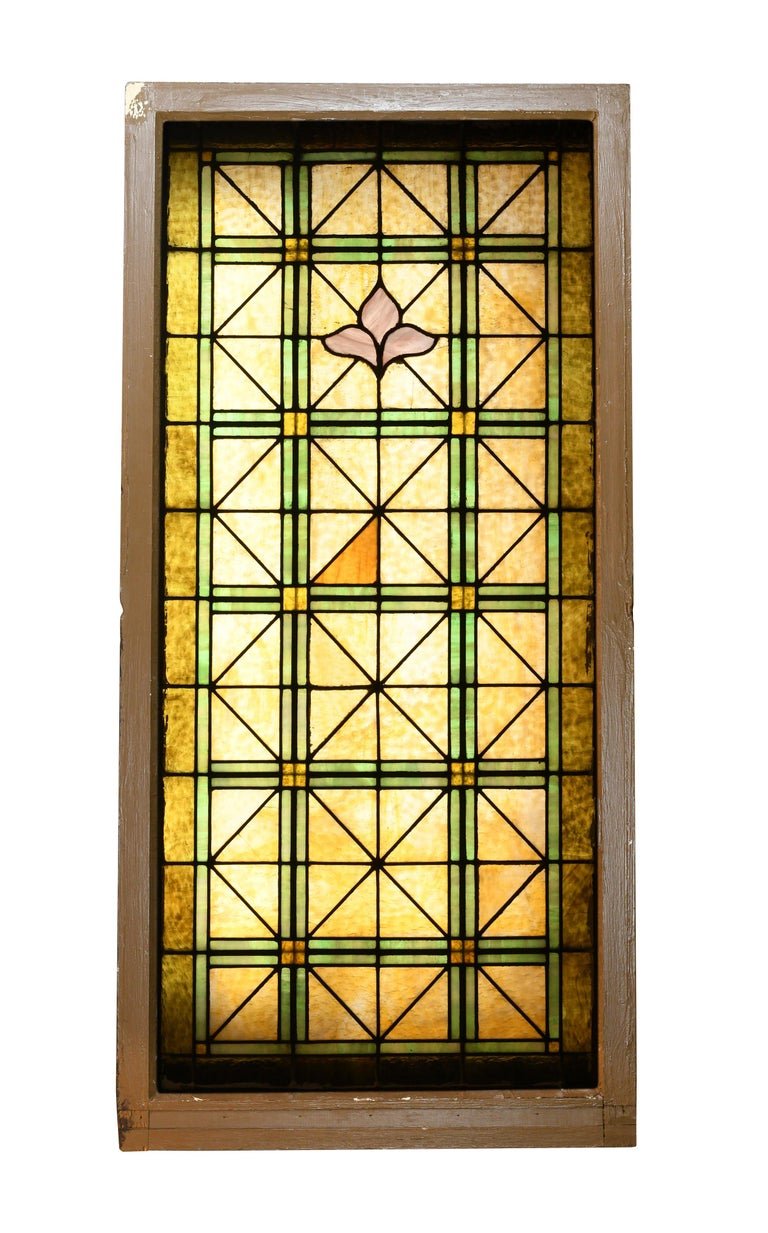 Beautiful stained glass church window divided into neat and tidy triangular shapes. Green glass pieces border heavily textured amber glass throughout, and a stylized purple fleur de lis creates a beautiful focal point near the top of the window.