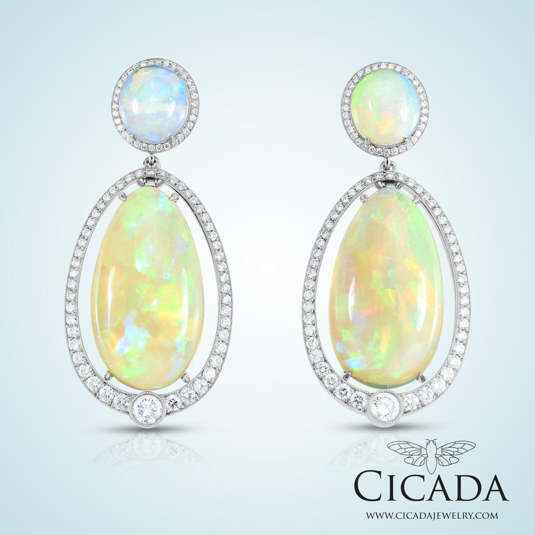 These platinum dangle earrings feature two pairs of stunning opals, surrounded by melee diamonds and set in platinum.  Opals: 30.96ct Diamonds: 1.55ct Metal: Platinum Dimensions: 1.6 inches wide x 2.25 inches long  Original piece by Cicada,