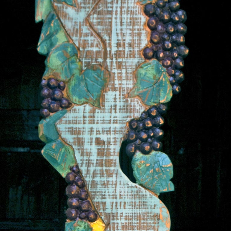 This superb panel-sculpture is part of a limited series of 5 one of a kind pieces dedicated to the harvest season portraying a woman in the act of picking grapes. A symbol of life and fertility, the female body is closely connected to the wood: the