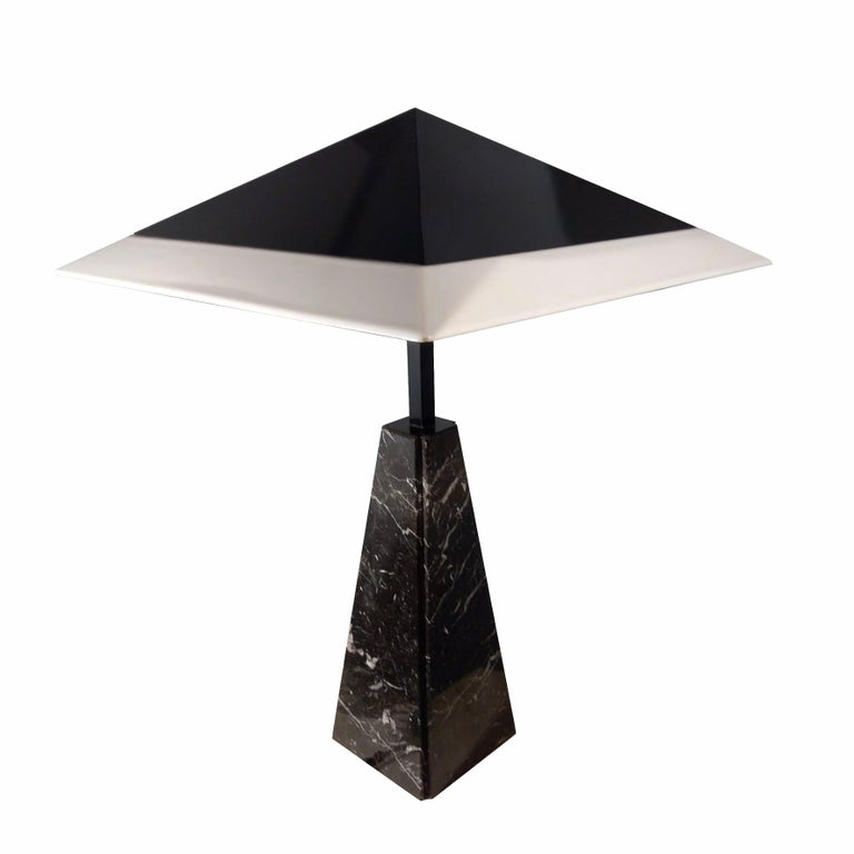 A tall table lamp, with a black lacquered and white perspex pyramidal lampshade on a black marble pyramidal base. Produced by Tronconi, Italy. Circa 1978.  Dimensions Height: 92 cm Side : 63 cm   Literature Cecilia Avogadro, Cini Boeri,