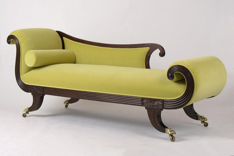 This English Empire style chaise lounge early 1800s is made out of solid Flemish mahogany wood and has been professionally restored. It features a scrolling design on the back armrest and legs and has remarkable hand carved details. The frame has