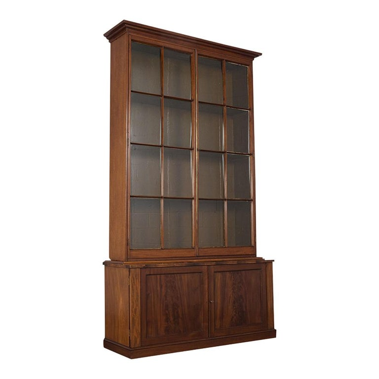 This circa 1840s English mahogany wood Regency style two doors bookcase is a beautiful piece that has been completely restored and features its original dark mahogany finish. It also has two tall glass panels doors divided with very fine molding