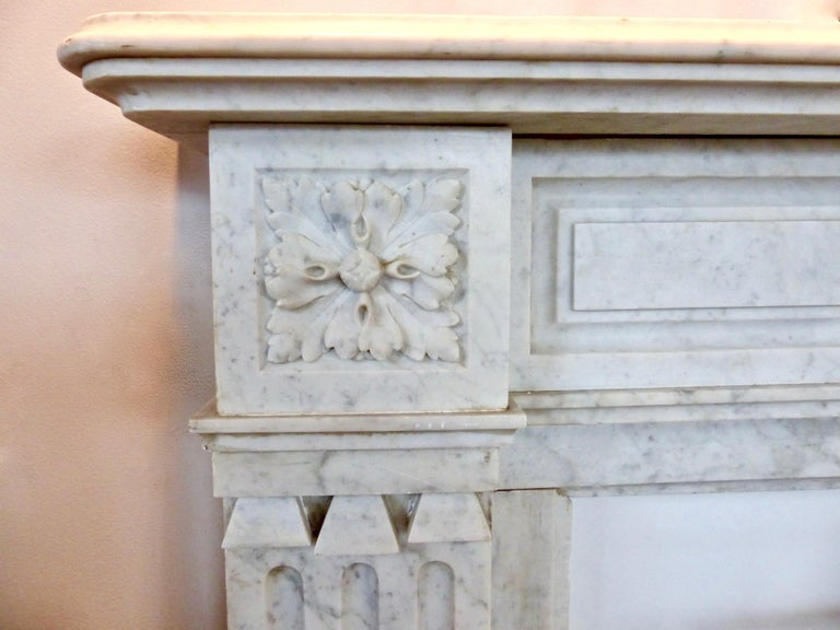 A French, handcrafted fireplace mantel/surround, circa 1860. Made from white Carrara marble with subtle decorative touches throughout, including unusual tiny scroll-work in its columns. Featuring a tiered top, with rounded edges, and a hand carved