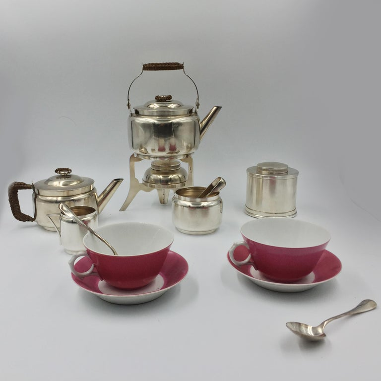 Christopher Dresser tea metal is in dark blue-grained leather. The design is the number # 85275. In very good condition with its original pieces. Silverware is from England and pink teacups and saucers from Limoges in France. This tea travel