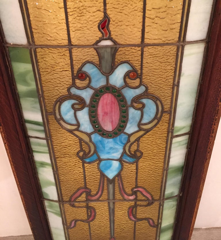 Original 19th century stained glass panel with wood frame. The shield pattern centered flanked by ribbons with an amber background. The outside edge with a green marbleized border. One small panel of glass with a slight crack. The entire stained