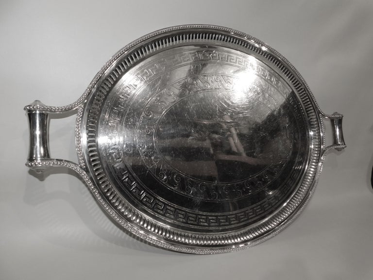 Large 19th century silver plated serving tray with ornate trim and handles.
