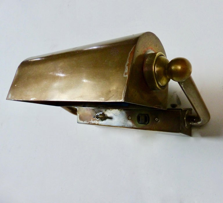 """Brass picture-style, wall-mounted lights with articulating hooded shades, circa 1920. Attractive cast brass support arms. Re-wired and CSA approved to current electrical standards. Price per light. Dimensions: 8"""" H x 112"""" W x 7"""" D Rare form. Very"""