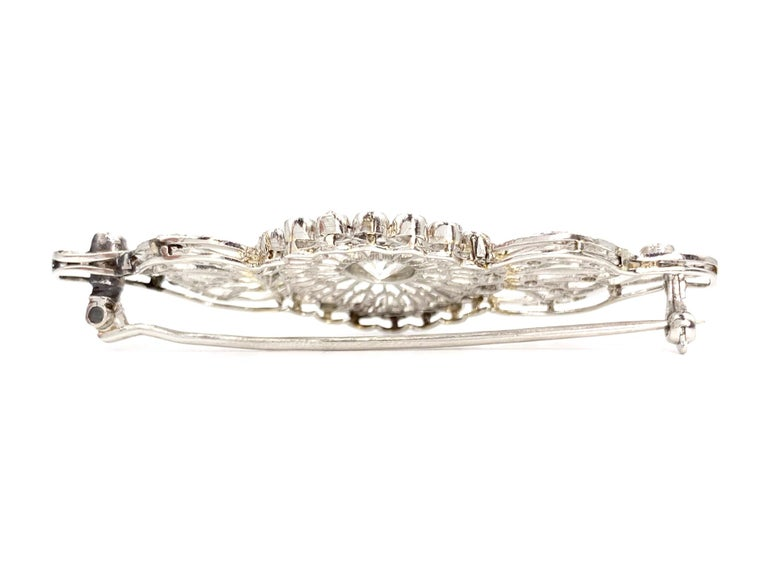 Made with fine craftsmanship with an airy feminine style, this 14 karat white gold Edwardian style diamond brooch showcases a center Old European cut white diamond, weighing approximately .80 carats at approximately G color, SI1 clarity. Center