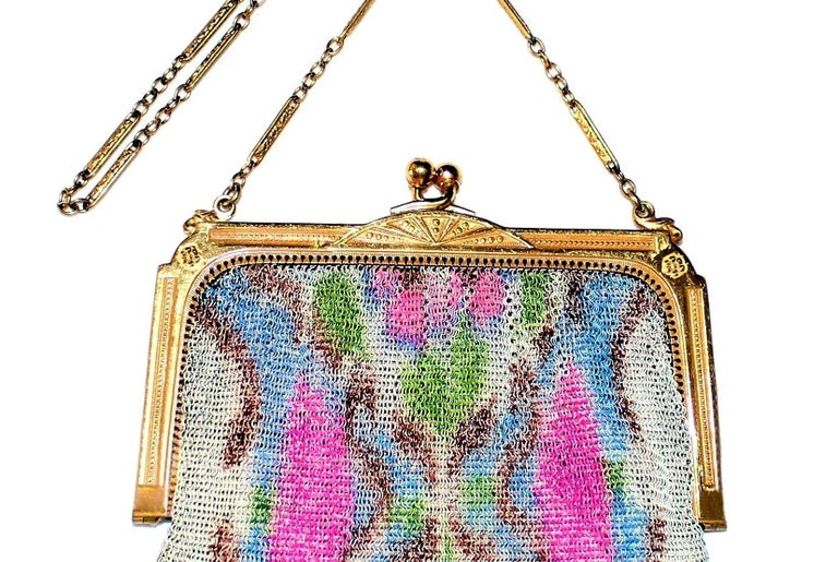 Circa 1920s to 1930s Whiting & Davis delicate gold tone metal mesh purse embellished with a bright floral motif, hanging from a bright gold tone metal frame.  Inside is a pale-peach satin lining that has a gathered side pocket with a small, round