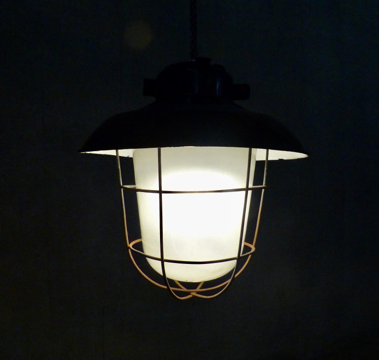 Set of four circa 1930 black enamel industrial lights from Europe. Complete with moulded glass shade and wire cage. Re-wired and inspected and approved to current electrical standards; ceiling mounting plates included. Currently hangs at eight feet