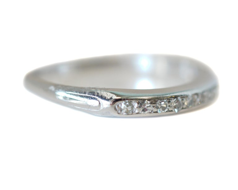 Description:  This beautiful 1930's Art Deco piece contains 8 gorgeous G color VS diamonds set in a row along the band which is platinum! With a dainty design on both sides of the diamonds. The total carat weight is .08 for the antique single cut