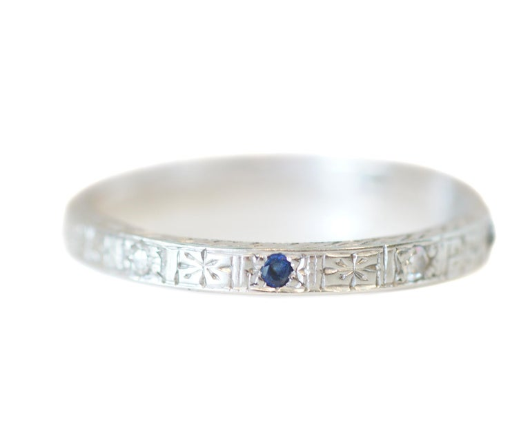 Description:  This piece is a 1930s Art Deco style 18K white gold wedding band with alternating diamonds and blue sapphires. The gems are spaced evenly around the beautifully engraved band.  A perfect band with a just enough pop of color that will