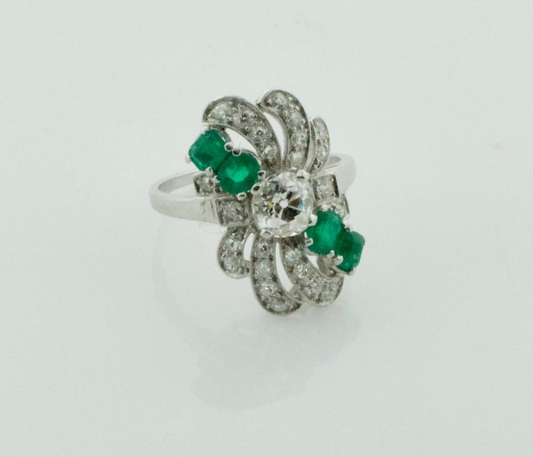 Circa 1930's Diamond and Emerald Ring in Platinum One Old Mine Cut Diamond weighing .50 carats approximately [Near Colorless and Si1 no imperfections visible to the naked eye] Four Cushion Cut Emeralds weighing .50 carats approximately Twenty Four