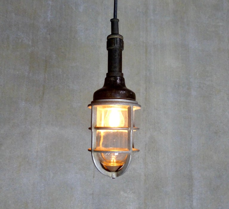 """A circa 1940 General Electric industrial """"trouble light' converted into a pendant. Cast metal cage and glass shade with a Bakelite topper. Re-wired and inspected and approved to current electrical standards; ceiling mounting plate included."""