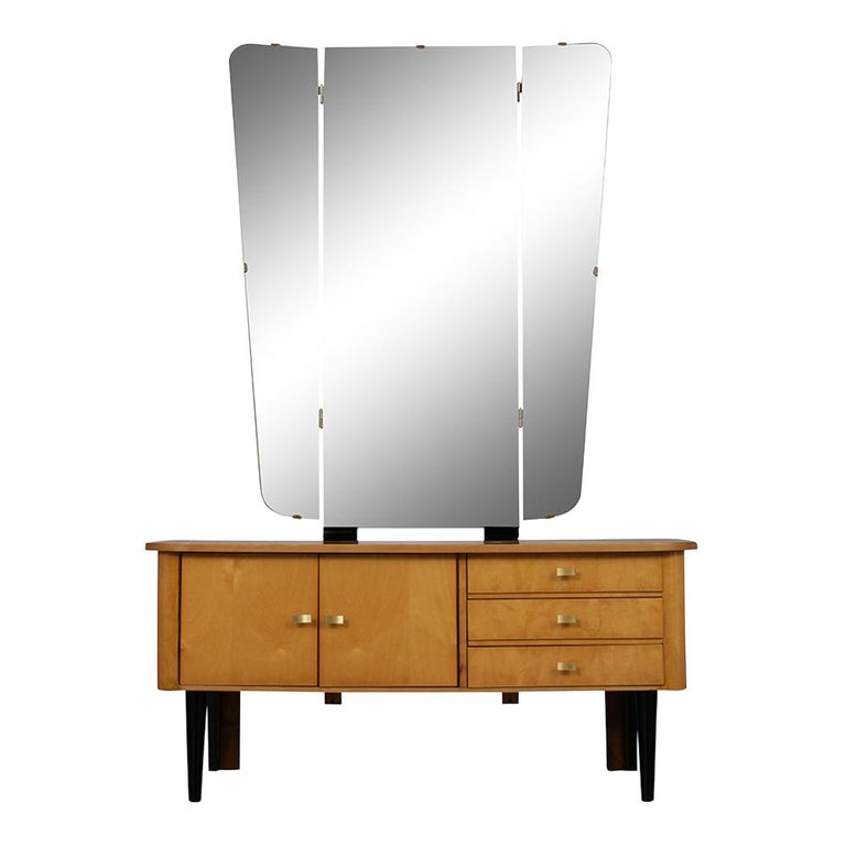 This 1960s modern-style German Vanity is made of maple wood has been stained end maple color with a lacquered finish. The vanity has a large foldable mirror, features three pull out drawers with brass pulls, and 2 open doors with brass handles. The