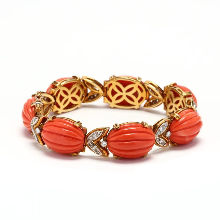 Circa 1970's, 18 karat yellow and white gold coral and diamond bracelet by Tiffany & Company. Alternating carved, oval coral links with diamond set leaf motif links with a box clasp.  Stones: - coral, 7 stones - oval corrugated cabochon - 18 x 13.25