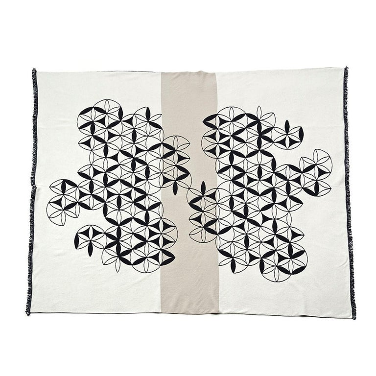 A series of geometric motifs are connected together in an abstract pattern to create a mesmerizing white motif that stands out over the dark grey of the background with a unique sense of movement. This jacquard knit decoration gives the blanket a
