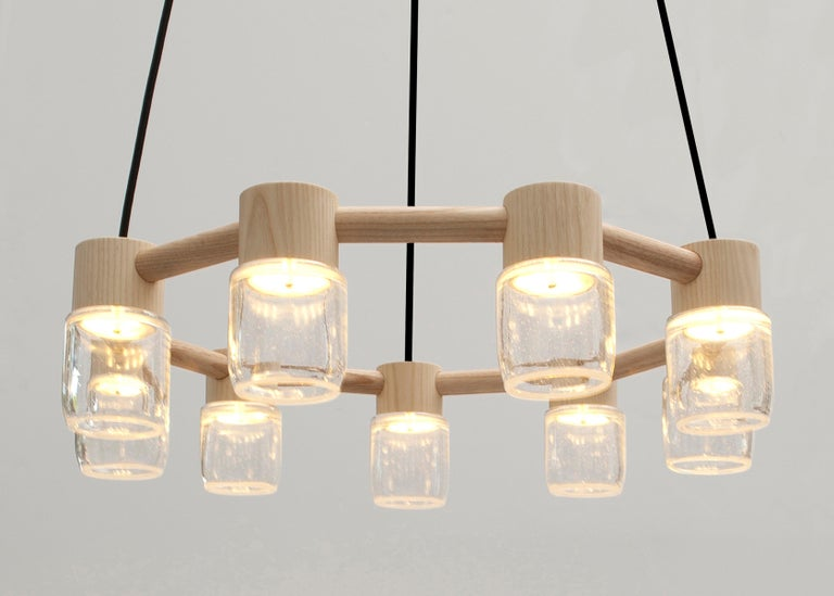 This handmade chandelier pairs a minimal solid wood canopy with nine hand blown glass diffusers. Efficient LED lighting components are neatly hidden in each canopy allowing the glass diffusers to illuminate without a visible bulb. 