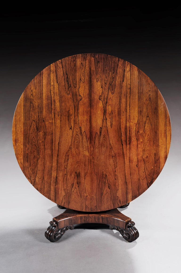 A well figured 19th century rosewood dining/center table on quadraform base,  English, circa 1840.   Of good proportions, the adjustable circular well figured bookmatch veneered rosewood top sits over a spreading octagonal columned with lotus