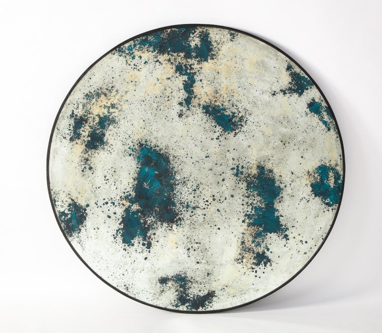 A circular mirror featuring an acid-washed mirror plate. This purposefully distressed mirror serves as an elegant but understated wall decoration. A statement piece in any room, this mirror gives the illusion that you have your very own full moon