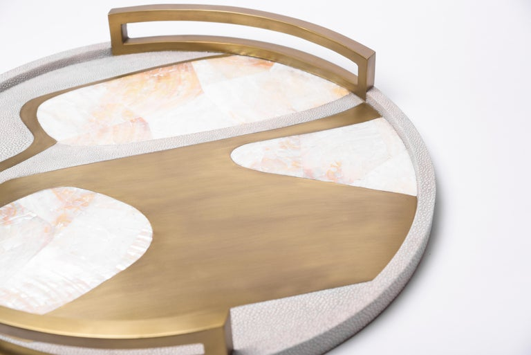 The Cosmos circular tray is a stunning tabletop piece for any space. Available in light or dark color way inlaid in a mixture of shagreen, pen shell and bronze-patina brass.  · Measures: 48.5 diameter x 6.3 cm  All R & Y Augousti pieces are