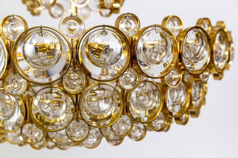 A Mid-Century Modern Palwa chandelier with a complex, multi tier design with 11 lights; a gilded brass, circular structure comprised of small and large rings with dangling optical glass lens crystals inside. 5 candelabra and 6 medium base, porcelain