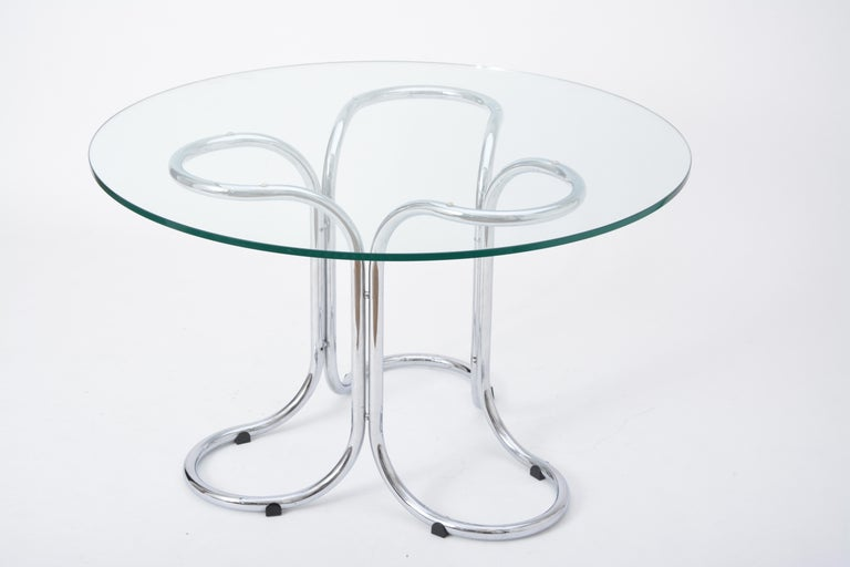 Circular Mid-Century Modern glass table in the style of Giotto Stoppino  This glass table was produced in the style of Giotto Stoppino. It is made from a chromed steel base which resembles the shape of a flower petal and a circular glass top.