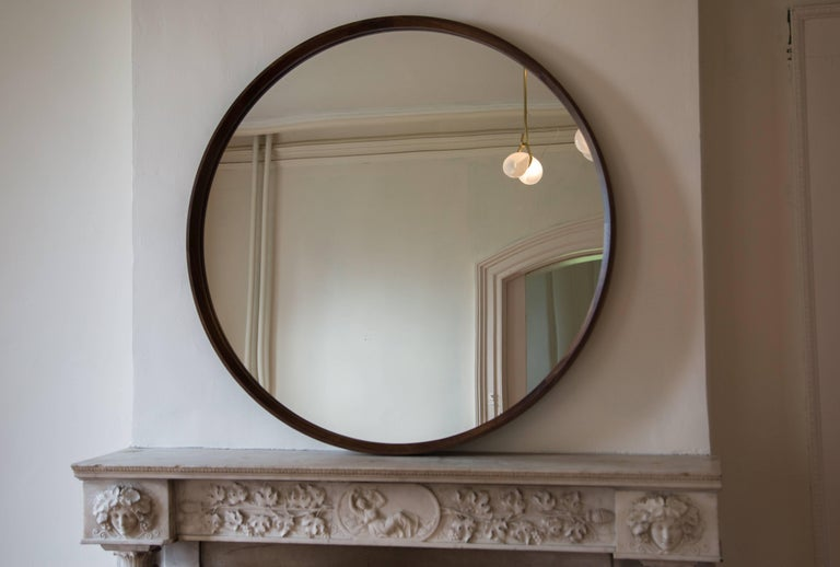 This simple, elegant mirror features a large interior bevel around the wooden frame creating a beautiful thin outer rim. Walnut frame shown in circular wall mounted version and rectangular full-length floor version.  Made to order in custom sizes,