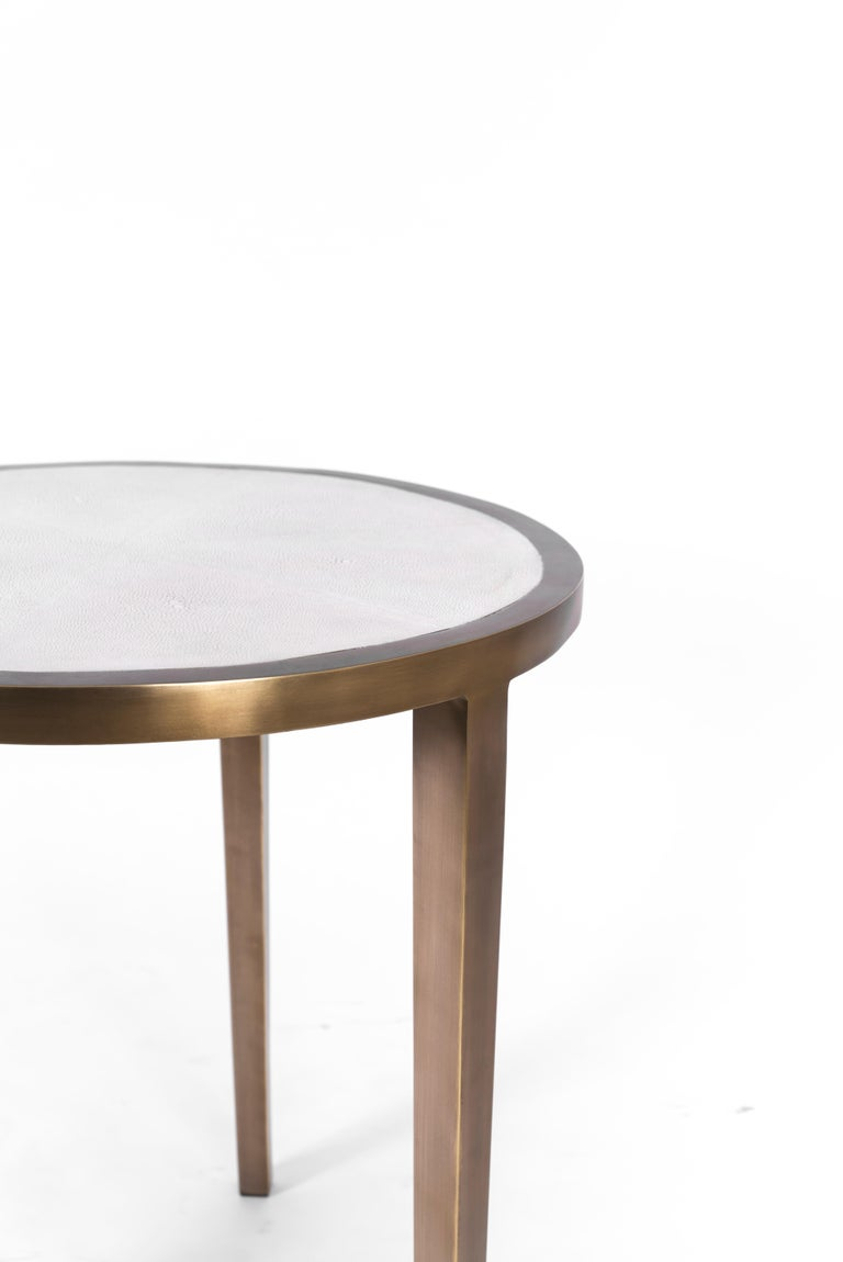 The circular side table inlaid in cream shagreen and bronze patina brass, is a classic piece that demonstrates the beautiful quality of Augousti pieces. The simplicity of this piece is elegant and adaptable to any space. Available in black shagreen,