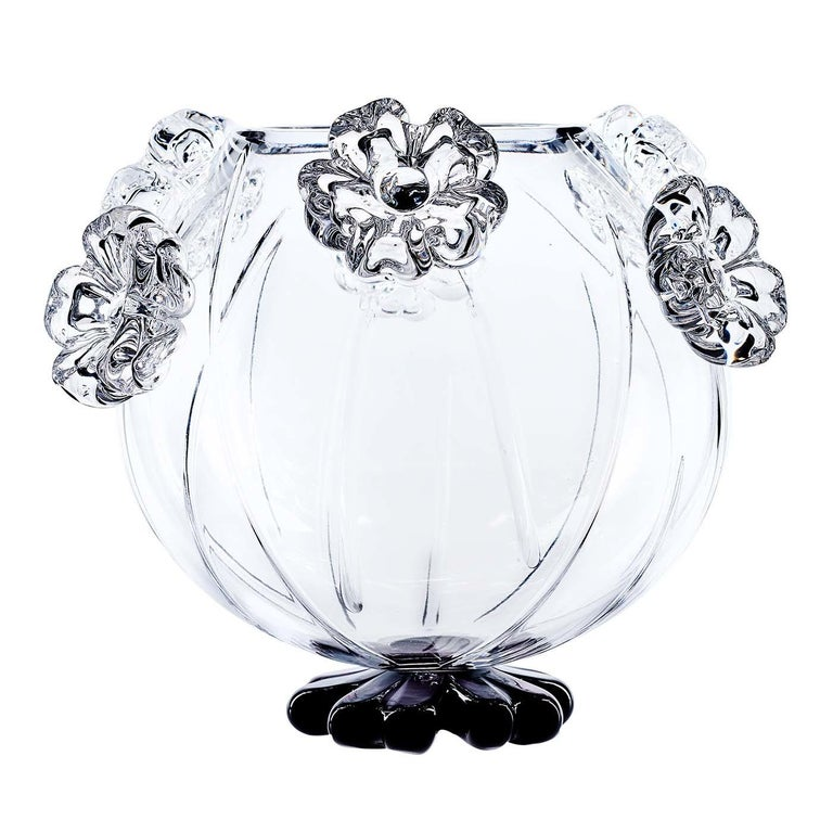 Part of the Cistus collection, this vase was completely handcrafted and is characterized by a round body of transparent crystal adorned with seven flowers positioned around the top at alternating heights, with a black base shaped like a flower.