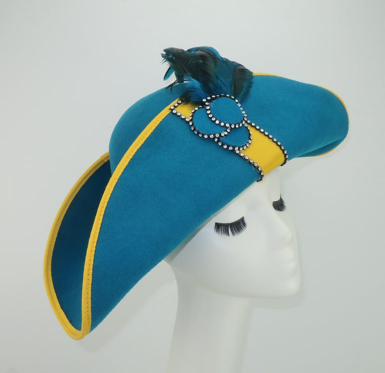 Citation creates a 1980's version of the bicorne hat in a brilliant shade of peacock blue contrasted with bright yellow grosgrain, rhinestones and a plume of feathers.  The wool body of the hat was fashioned by the Bollman Hat Co., an American hat