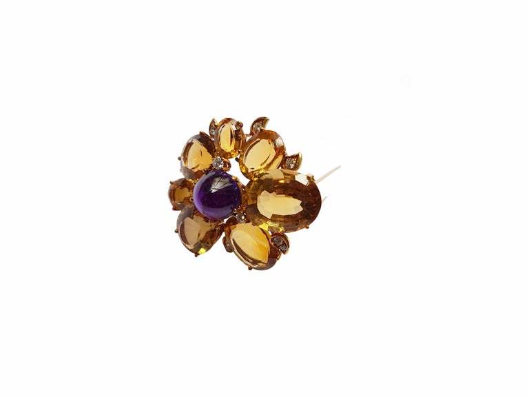 Gorgeous brooch, from Germany, ca. 1960 made of yellow gold. Seven beautiful honey-colored citrines in sizes from 7 x 10 mm to 17 x 20 mm surround the centered cone-shaped deep purple amethyst cabochon, 13,5 mm in diameter,  with