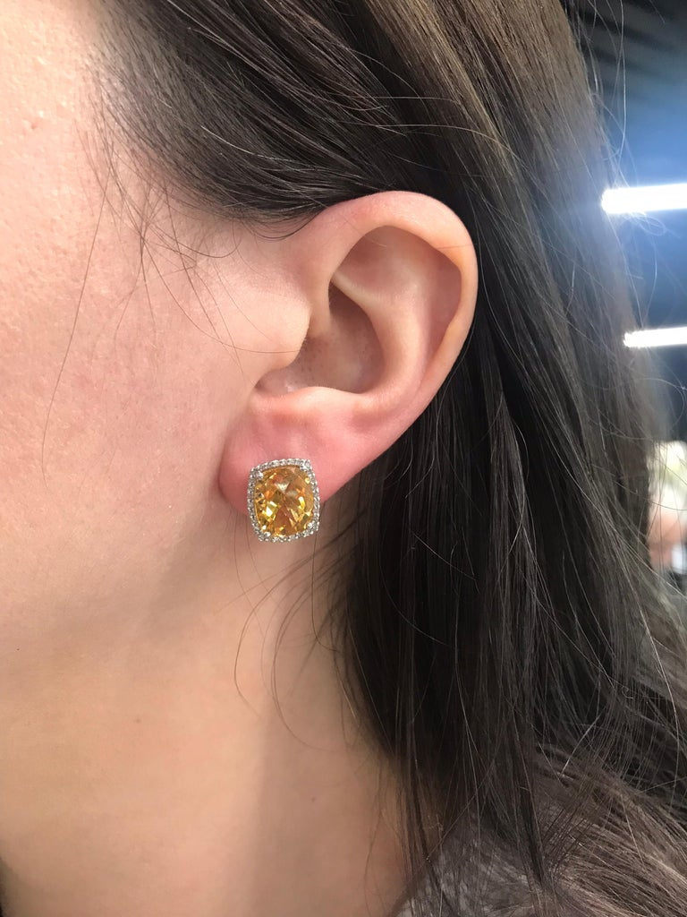 14K White gold stud earrings featuring two yellow Citrines measuring 11 * 9 mm flanked with round brilliants weighing 0.40 carats.