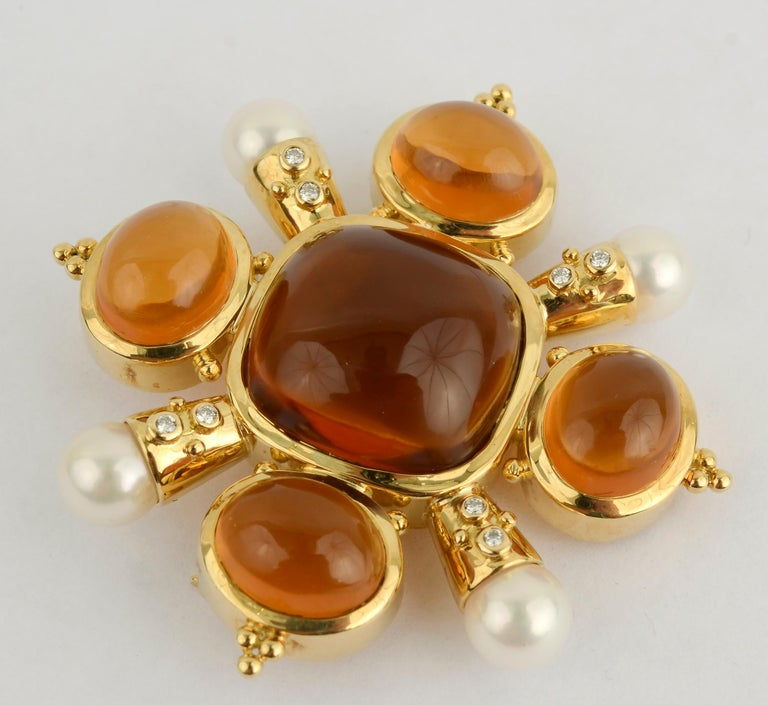 Striking brooch of warm, honey colored citrine; pearls and diamonds. Each of the arms supporting the pearls has two diamonds and two gold balls. The balls echo the tips of the oval citrines. The brooch measures 2 1/16 inches in diameter and 1 7/8