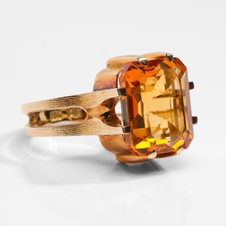 A rich, vividly-saturated natural citrine measuring approximately 12.27mm x 9.95 and weighing approximately 5 ¼ carats is the focal point of this truly unique, architectural ring from the Midcentury. While there is no maker's mark, the ring is