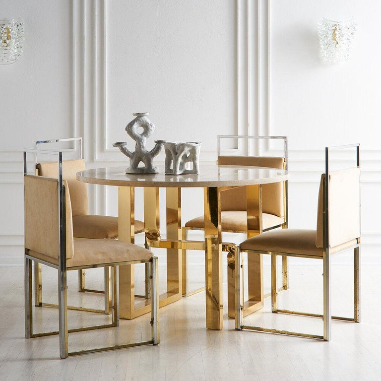 A remarkable and rare dining table by Cittone Oggi featuring a travertine stone top with artful brass inlay resting on a sculptural brass plate base, Italy, 1970s.  Matching dining chairs also available.   Dimensions: 31