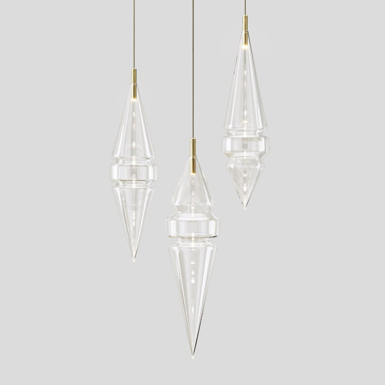 These mesmorising glass pendant lights are inspired by the scape of an imaginary city. Shapes and silhouettes, peaks and towers of a futuristic dreamscape.  The precision of uniquely skilled medical glass manufacturers made this possible, a