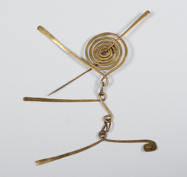 Articulated brass brooch and earrings by the artist Claire Falkenstein. The spiral on the brooch rotates on the pin that pierces the through the center of it. The arms below are like a small mobile. On one pair of earrings the inner spiral rotates