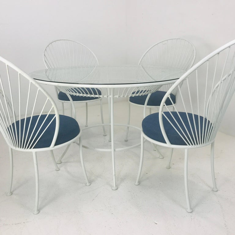 Five piece clamshell patio set in the style of Salterini. Original and vintage, circa 1970s. Five pieces included are a four chairs with upholstered seats and round center table. Table measures 48