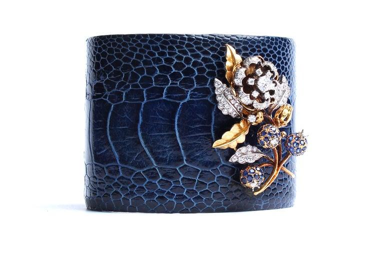 Cuff bracelet made of blue crocodile skin. Adjustable.  14k gold, diamond, sapphire, enamel flower charm attached.