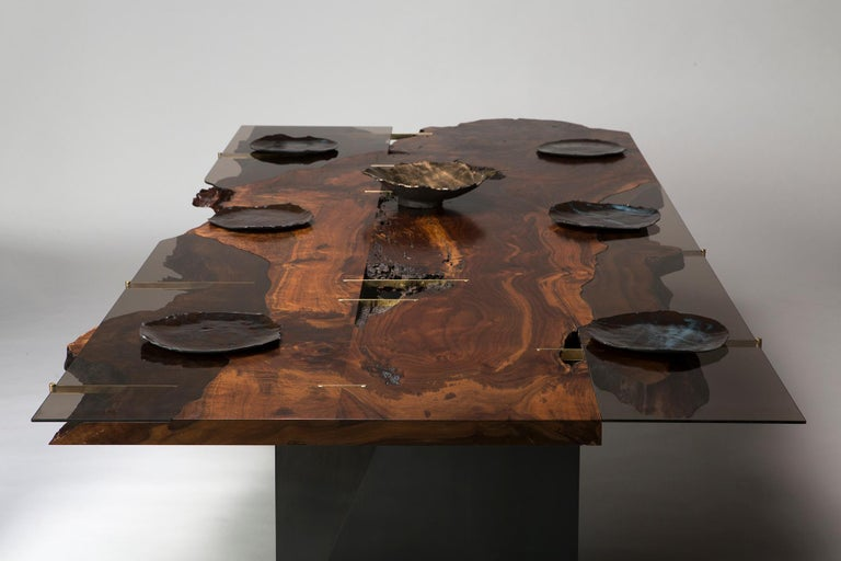This live edge Claro walnut and bronzed glass dining table features a stunning array of detail and craftsmanship. Beginning with a bookmatched set of musical grade Claro walnut slabs, Taylor Donsker methodically insets three sheets of bronzed glass