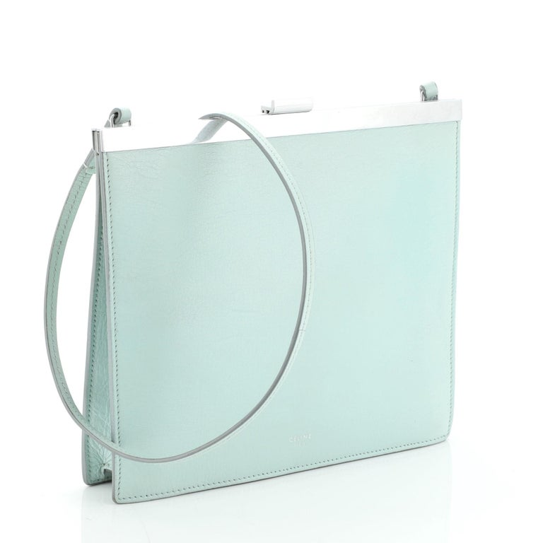 This Celine Clasp Crossbody Bag Leather Mini, crafted in green leather, features slim leather shoulder strap, stamped Celine logo, framed top, and silver-tone hardware. Its clasp closure opens to a yellow leather interior with slip pockets.