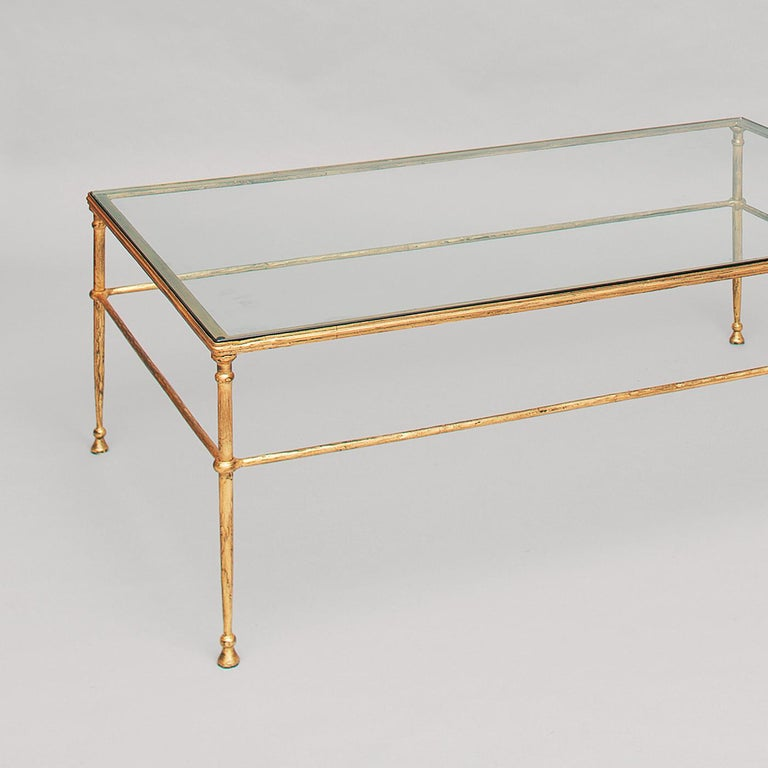 The sophisticated design of this tall coffee table evokes ancient Roman and Etruscan furniture, with their slender metal structures and harmonious proportions. The table's forged iron elements create a net of delicate lines adorned with rings at