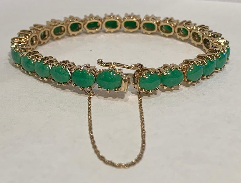 Lovely estate tennis or line bracelet features 25 matched, bright apple green, polished oval jade cabochons mounted in 6 prong, hinged 14 karat yellow gold stations. A timeless and classic style that is easy to wear! Bracelet has a tongue and box