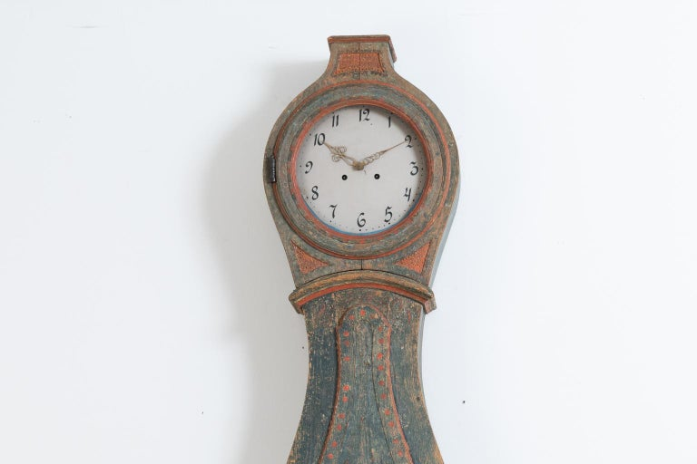 Classic Rococo long case clock from northern Sweden. More specifically the County of Hälsingland. The clock is dry scraped to its original blue and red paint. The iron hinges on the doors are handcrafted and unusually well-made. The ring has old
