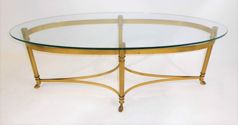 Fine 1970s Labarge brass long oval coffee table featuring modern Hollywood Regency lines with Louis XVI styling with hooved feet and a new glass top. The styling reminding one of Maison Jansen table designs. The glass is new and the brass exhibits a