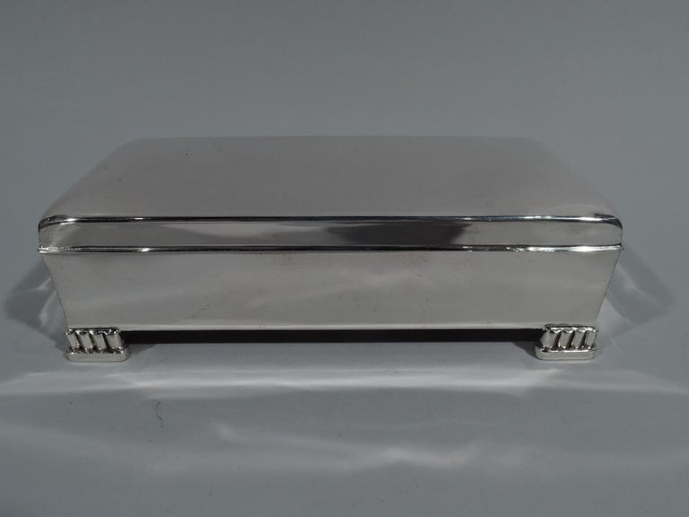 Classic Mid-Century Modern sterling silver box. Made by Poole in Taunton, Mass. Rectangular with straight sides. Cover hinged with curved top, straight sides, and flat overhanging rim. Corner supports in form of bracket colonnade on base. Box