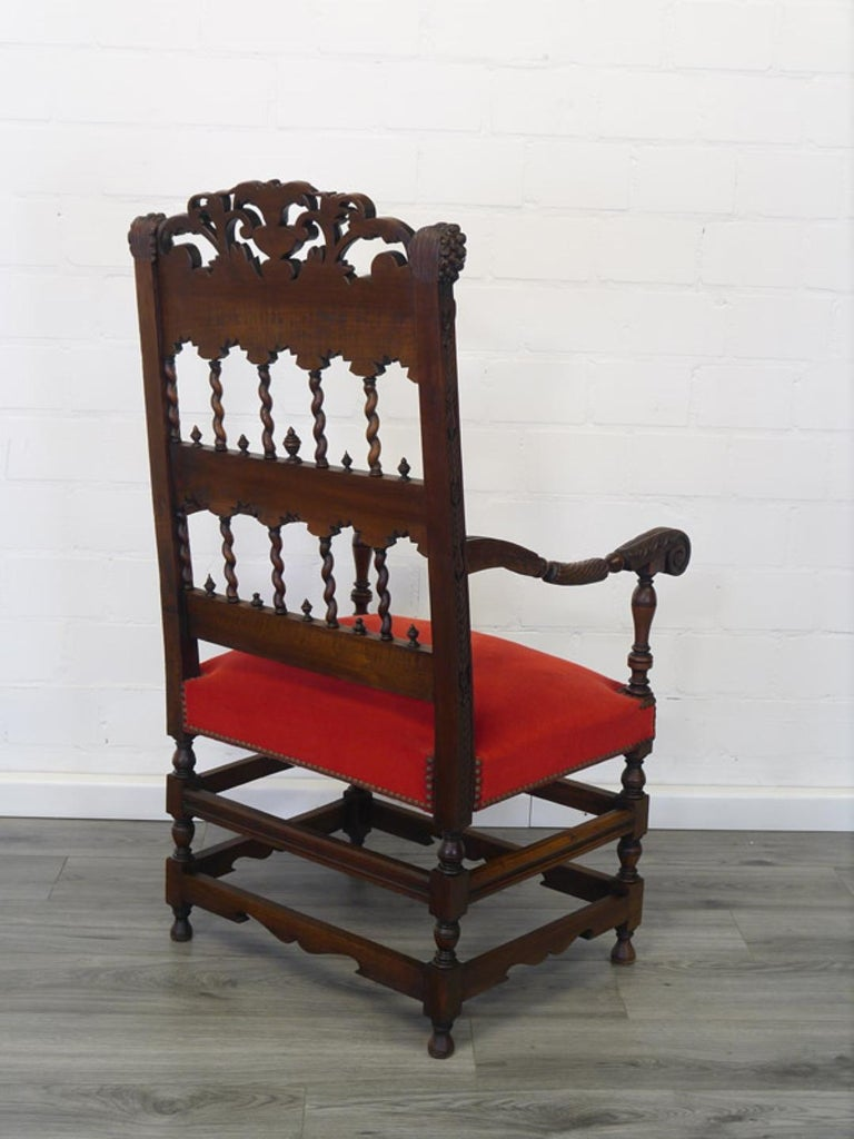 Classic antique armchair with a Renaissance design from the Revival period circa 1880. Made out of solid walnut wood and covered with a red velvet upholstery with round headed nails. The backrest if decorated with stunningly carved ornamentations,